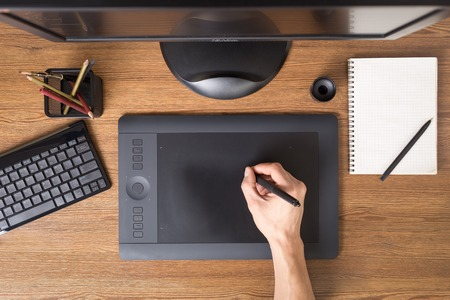designer: Designer using graphic tablet in the office. Top view workplace with tablet, keyboard and computer.