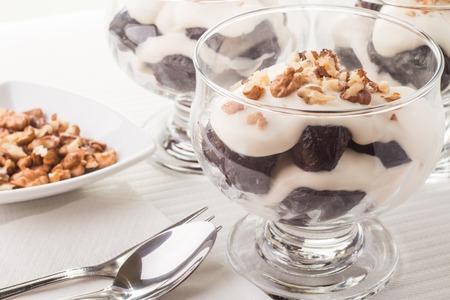 ciruela pasa: Postre con ciruelas, nueces y crema batida en bowles de vidrio sobre la mesa