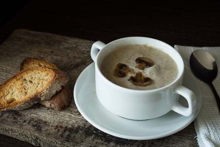 mushroom soup: Creamy mushroom soup with slice of bread on wood background