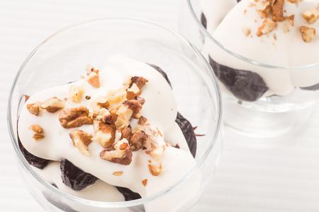 podar: Postre con ciruelas, nueces y crema batida en bowles de vidrio sobre la mesa