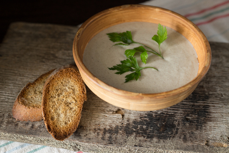 mushroom soup: Mushroom soup puree with parsley in ceramic bowl with slice of bread on kitchen towel. Rural style meal time background Stock Photo