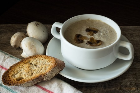 mushroom soup: Bowl of mushroom soup puree with a few mushrooms and toasts around on wooden table