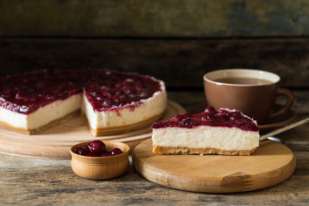 cherry: Slice of cheesecake with cherry and cup of tea on wooden background