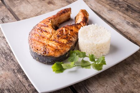 Big grilled salmon steak with rice on the plate on wooden table. Healthy seafood menu or recipe background