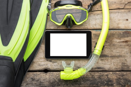 snorkelling: Scuba diving or snorkelling lesson template mock-up background. Flippers, mask, snorkel with blank tablet PC on wood background Stock Photo