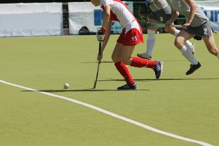 hockey sobre cesped: Mujer jugadores de hockey sobre hierba con la bola en la hierba. equipos profesionales j�venes en la competencia