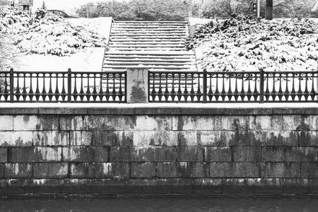 old bridge: Old brick embankment of the river with stairs in winter. Black and white image Stock Photo