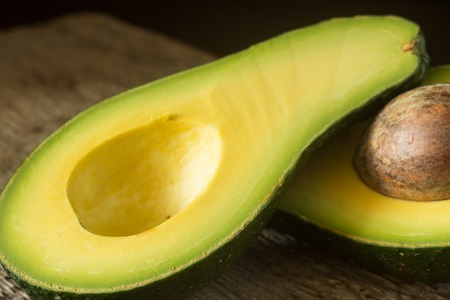 halved: Halved avocado on old wooden board. Close up image
