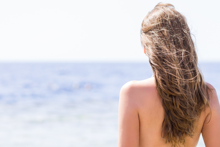 weather: Young woman with long curly hair standing near the sea