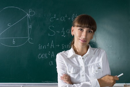jovenes estudiantes: Mujer joven del profesor o ni�a estudiante en la pizarra con la ecuaci�n matem�tica