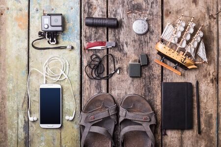 torch: Mens travelling stuff mock up on wood background. Smartphone, action camera, notebook, torch, knife, sandals and model of sailing ship