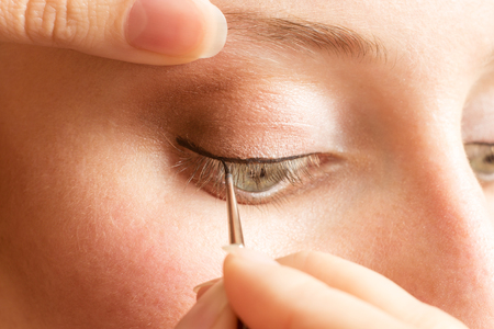 and eyelid: Beautician applying eyeliner on the eyelid. Professional Make-up background