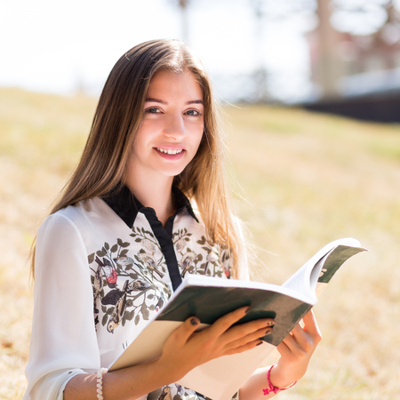 workbook: Young european female student with workbook at outdoors on warm sunny day. Smiling girl with book sitting on the grass hill