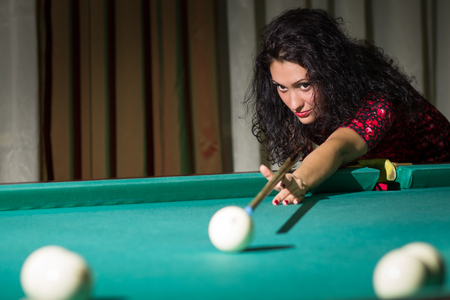 frizzy hair: Young attractive woman with dark frizzy hair hitting ball with cue playing billiards. Pool game background