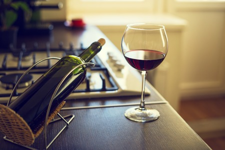 worktop: Glass of red wine with bottle near a cooker on the kitchen worktop. Stock Photo
