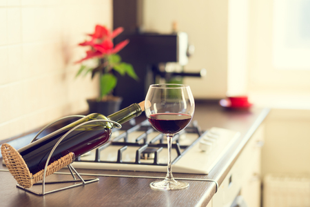 worktop: Glass of red wine with bottle and plant in pot on the kitchen worktop near stove Stock Photo