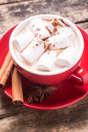 badian: Red cup of hot chocolate or cocoa with white marshmallow on wood table. Close up image of hot drink