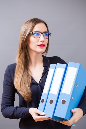 ring binder: Young beautiful business woman in glasses with pile of blue ring binder. Accountant on the work