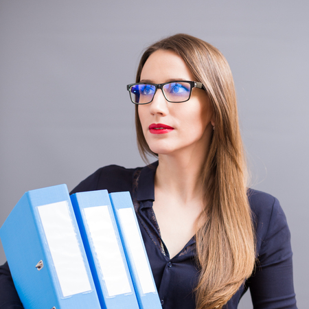 Young beautiful business woman in glasses with pile of blue ring binder. Accountant on the work