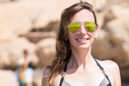 Young beautiful happy girl in sunglasses and bikini standing at the beach Stock Photo