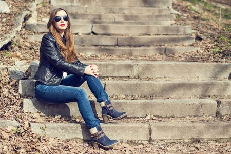 Young woman in jeans and leather jacket resting on the park stairs. Attractive girl with long hair sitting on steps