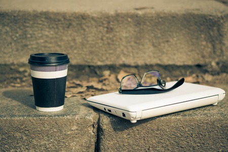 Mug of coffee with white laptop and protective glasses on the steps. Warm color toned image Stock Photo
