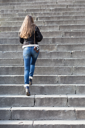 upstairs: Young woman with old camera steps upstairs at the outdoor