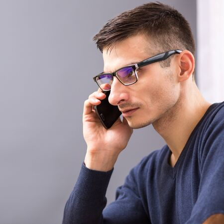 Young business man in glasses speaking on the phone. Adult caucasian man talking on cellphone at his workplace