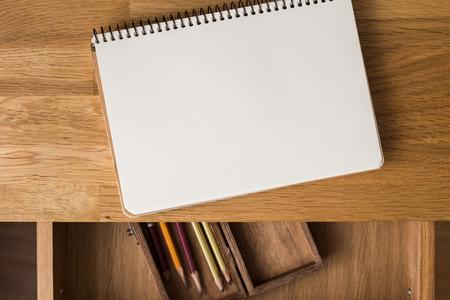 hoja en blanco: Cuaderno en blanco con lápices en la caja sobre la mesa. vista aérea Foto de archivo