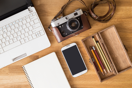 office use: Mock up of photographer desk with laptop, note, phone, camera and pencils in wooden box. Top view image of designer or traveller workplace