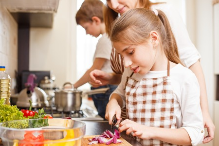 Family cooking background. Mum and daughter cutting onion for salad in the kitchen Stock Photo