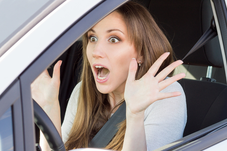 stared: Frightened young car driver woman looking straight ahead. Shocked beauty girl in a car Stock Photo
