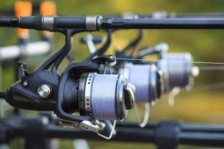Three fishing rods with professional reel set up on support.