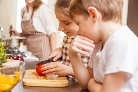 Fun family cooking background. Children preparing salad at the kitchen counter