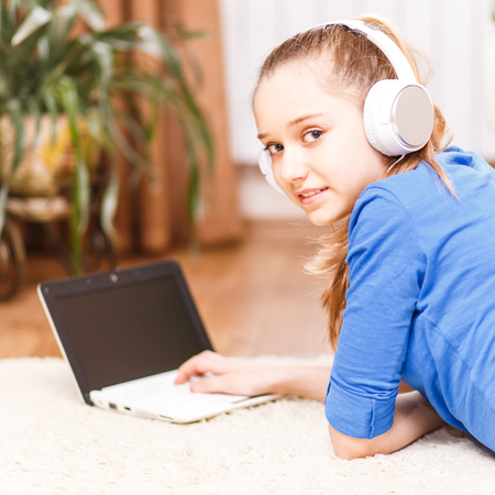 homestudy: Teenage smiling girl with white headphones using laptop on the floor. Smiling teenager with laptop at home. On-line education background