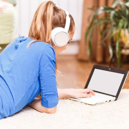 homestudy: Teenage smiling girl with white headphones using laptop on the floor