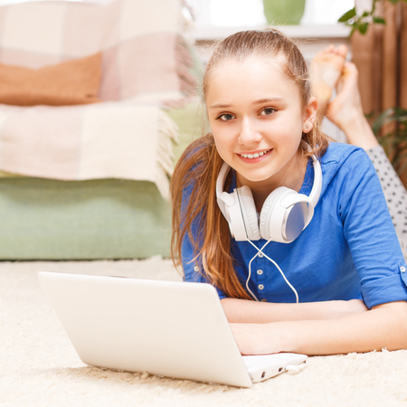 homestudy: Teenage smiling blonde girl with white headphones using laptop on the floor. Smiling teenager with laptop at home. On-line education background
