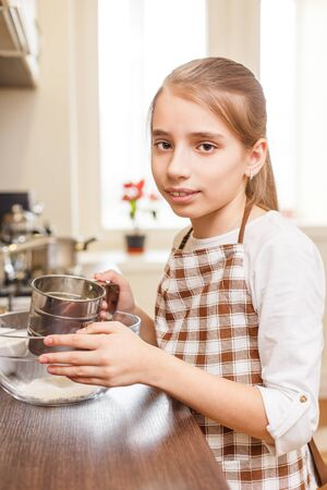 sieve: Young teenage girl sieving flour through the sieve at the kitchen counter Stock Photo