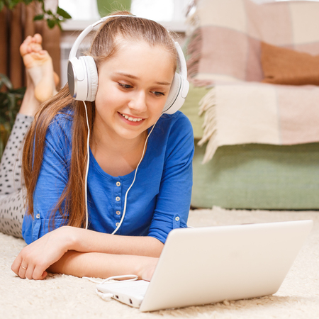 homestudy: Teenage smiling girl with white headphones using laptop on the floor. Smiling teenager studying with laptop at home. On-line education background
