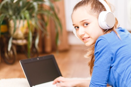 homestudy: Teenage smiling girl with white headphones using laptop on the floor. Smiling teenager looking into camera. Online education background Stock Photo
