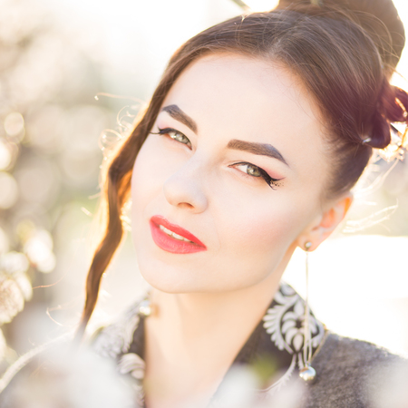 stage make up: Young attractive woman with japanese style makeup among blossoming tree in sunset beams. Beautiful asian girl with blooming trees