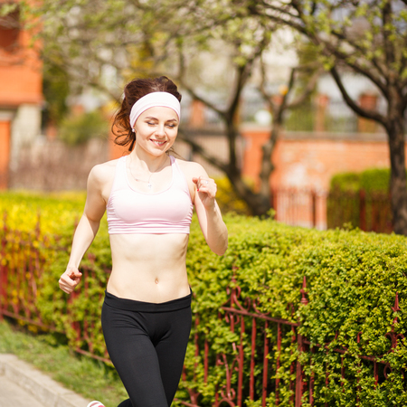 shrubbery: Young happy woman jogging along the street with green lush shrubbery. Smiling girl running outdoors on sunny day
