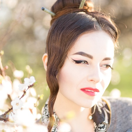 cherrytree: Beautiful young caucasian woman near blooming tree. Thoughtful girl with blossoming cherry-tree Stock Photo