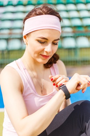 wristband: Young smiling sporty woman using smartwatch or other wearable device. Pretty slim caucasian girl use fitness wristband Stock Photo