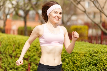 shrubbery: Young happy woman jogging along the street with green lush shrubbery