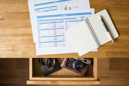 Bovenaanzicht bureau met accounts op en oude camera met notebook in open lade. Concept dromen werkplek vakantie achtergrond Stockfoto