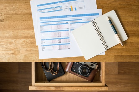 Top view desk with accounts on it and old camera with notebook in open drawer. Concept dreaming workplace vacation background Stock Photo