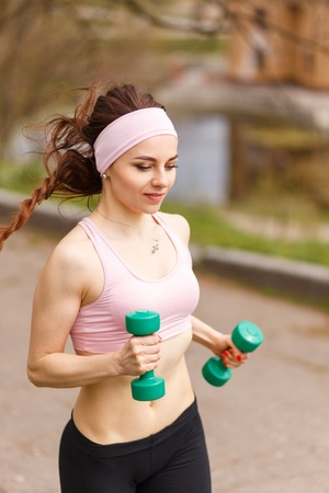 Young athletic woman jogging with dumbbells in park. Smiling girl in sportswear running on pathway