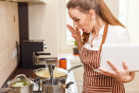 stared: Young woman trying cooking with recipe from laptop. Shocked caucasian woman online learning cooking