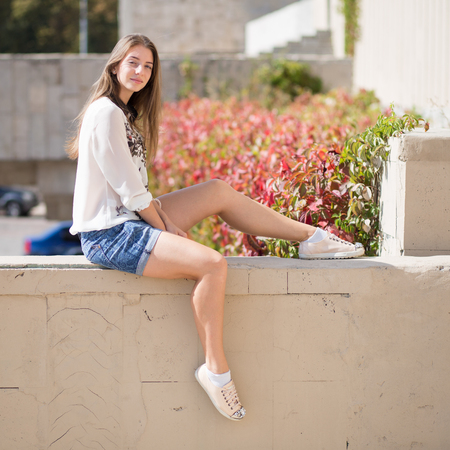 Young fashion student girl sitting on the brick wall. Outdoor portrait of Smiling girl in shorts and white shirt